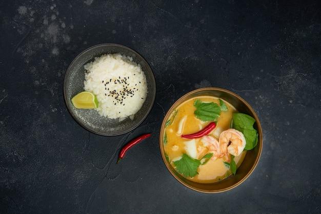 Zupa tom yam podawana z ryżem z góry na czarnym tle rustykalnym