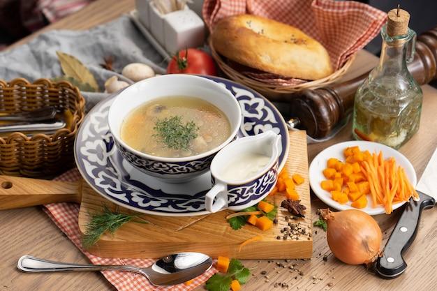 Zupa wegetariańska z pieczarkami, marchewką i koperkiem na talerzu z tradycyjnym uzbeckim
