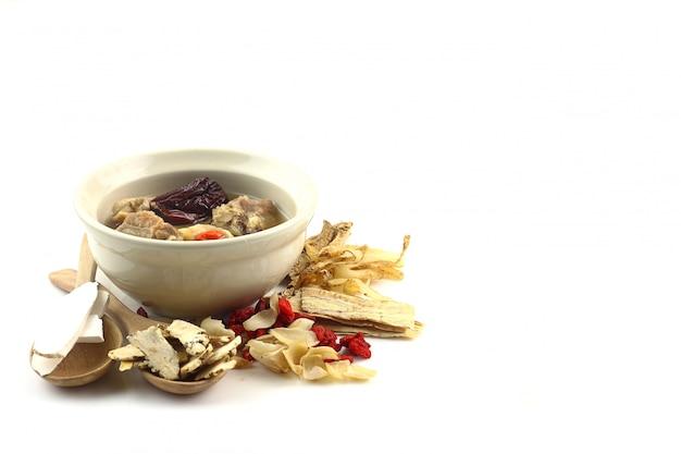 Zupa wieprzowa z chińską medycyną na białym tle
