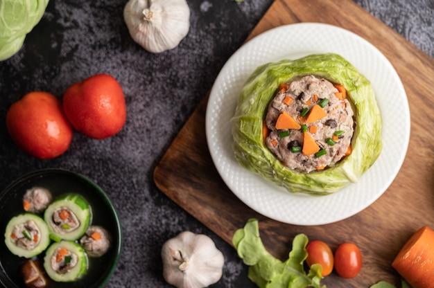 Zupa wieprzowa z marchewką, posiekaną zieloną cebulą, ogórek w drewnianym talerzu na drewnianym talerzu