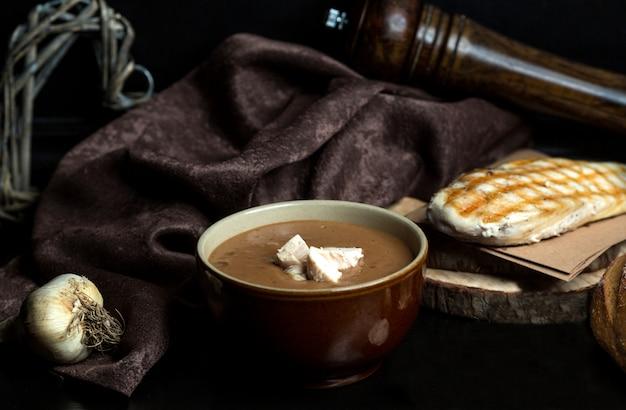 Zupa z czarnego groszku zwieńczona kawałkami kurczaka podawana w misce