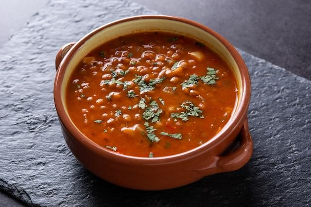 Zupa z czerwonej soczewicy na czarnym tle łupków