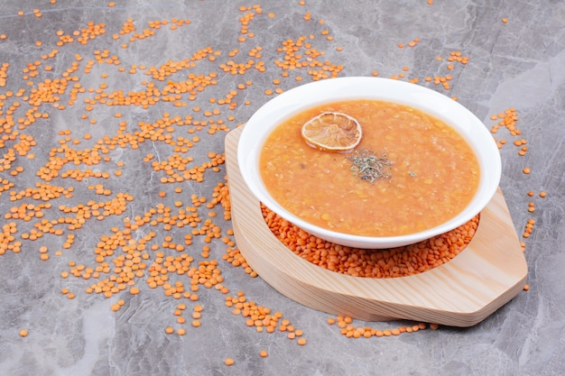 Zupa z czerwonej soczewicy na drewnianym talerzu na marmurze