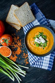 Zupa z czerwonej soczewicy ozdobiona świeżymi warzywami i zielenią.