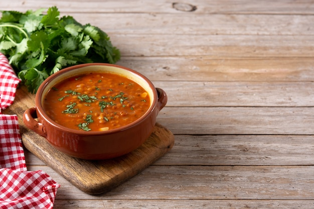Zupa z czerwonej soczewicy w misce na rustykalnym drewnianym stole