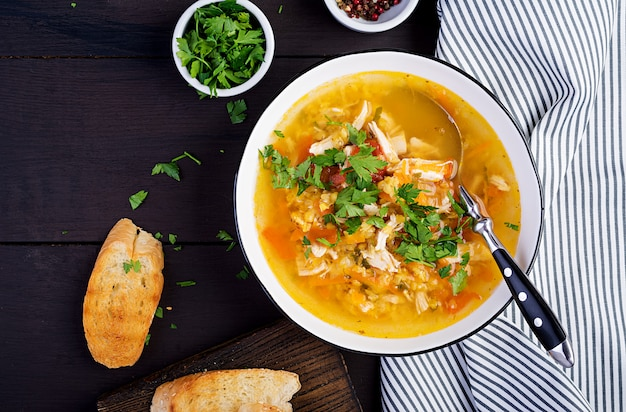 Zupa z czerwonej soczewicy z kurczakiem i warzywami z bliska na stole. zdrowe jedzenie. widok z góry