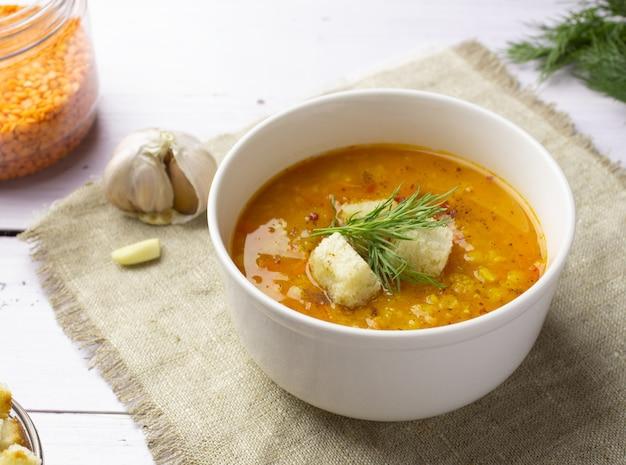 Zupa z czerwonej soczewicy ze składnikami na jasnym tle. tradycyjna turecka lub arabska pikantna zupa z soczewicy i warzyw, zdrowe wegańskie jedzenie. widok z boku