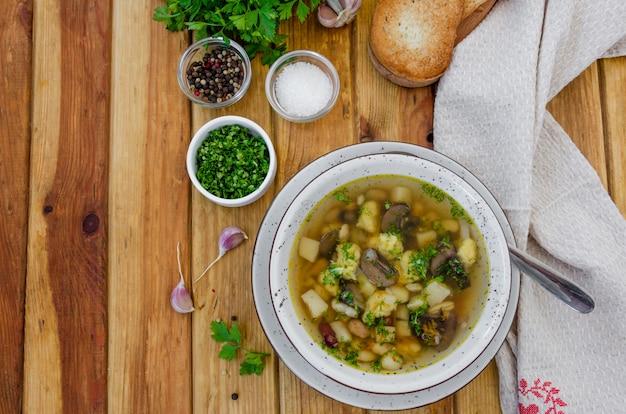 Zupa z fasolą, pieczarkami i pierogami w misce na ciemnej drewnianej powierzchni z ziołami i czosnkiem