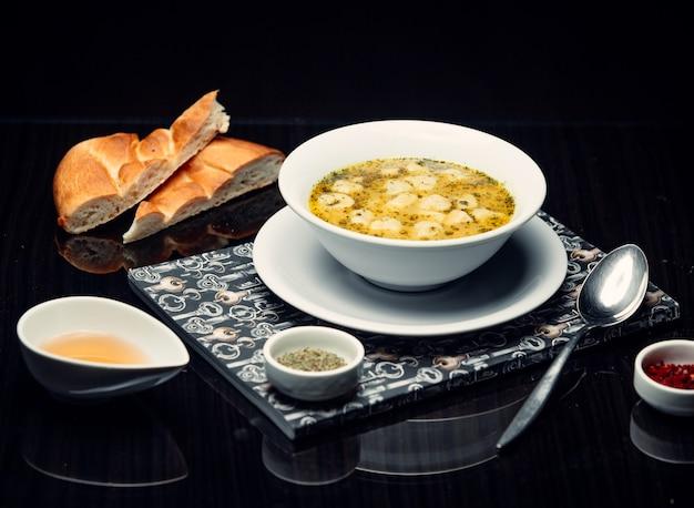 Zupa z kluskami dusbara pelmeni podawana z octem, suszoną miętą