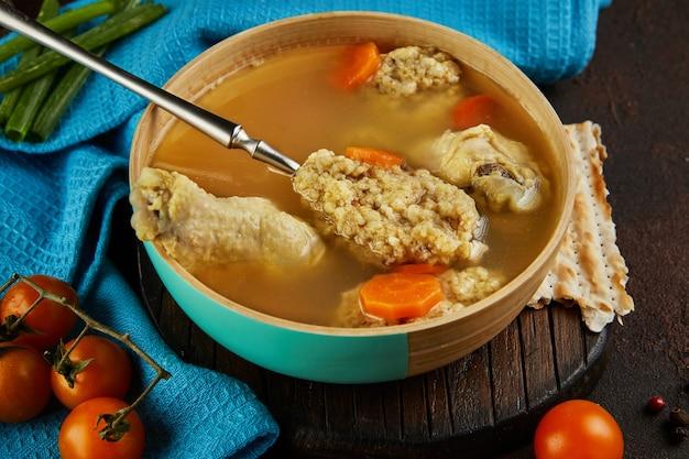 Zupa z kluskami z macy i kurczakiem z marchewką i pomidorami. zdrowe jedzenie na paschę.