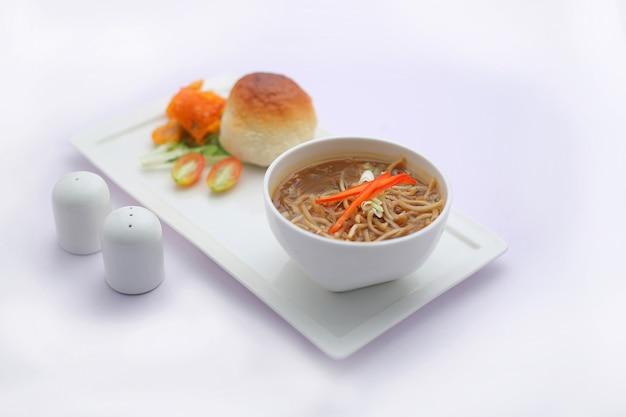 Zupa z kurczaka mandżurska przyozdobiona warzywami ułożona w białej misce