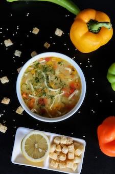 Zupa z kurczaka marchew makaron koperek pomidor cytryna krakersy pieprz widok z góry