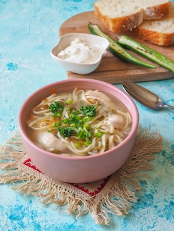 Zupa z kurczaka po rumuńsku i mołdawsku z makaronem. tradycyjna zupa kaca podawana jest z ostrą papryką i śmietaną.