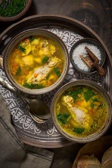 Zupa z kurczaka w stylu azjatyckim w dwóch glinianych misach, sól, widok z góry.