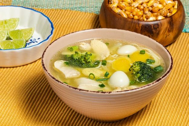 Zupa z kurczaka żeń-szenia z brokułami, jajkiem przepiórczym, cytryną i prażoną kukurydzą peruwiańską. tradycyjne jedzenie.