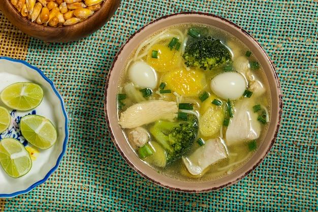 Zupa z kurczaka żeń-szenia z brokułami, jajkiem przepiórczym, cytryną i prażoną kukurydzą peruwiańską. widok z góry.