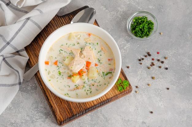Zupa z łososia ze śmietaną, ziemniakami, marchewką, ziołami i grzankami w misce.