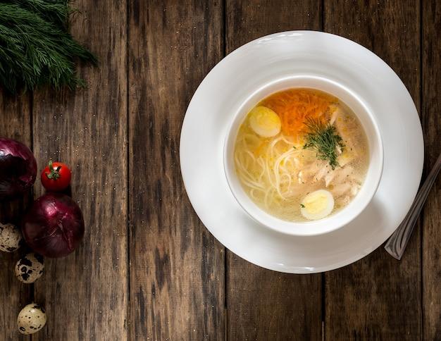 Zupa z makaronem i jajkami przepiórczymi na drewnianej powierzchni, widok z góry