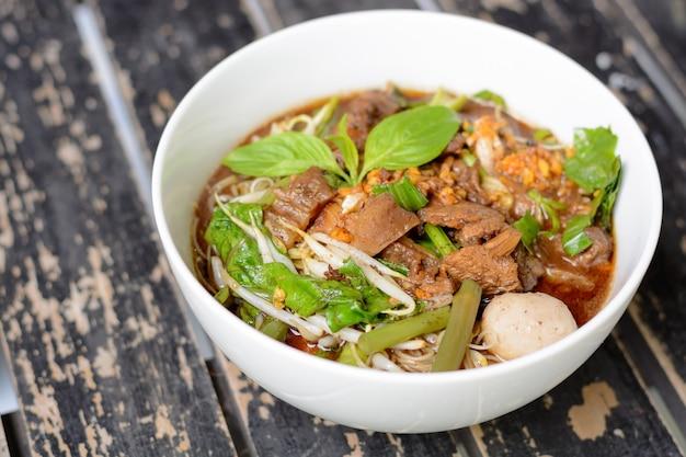 Zupa z makaronem o intensywnym smaku i wołowinie na drewnianym stole
