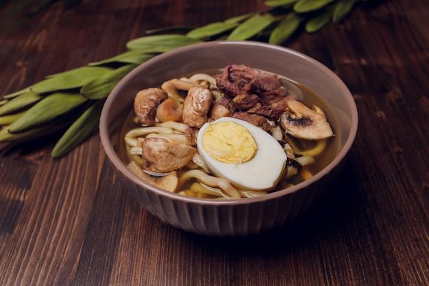 Zupa z makaronem ramen na drewnianej desce do krojenia ze świeżo pokrojoną cebulą