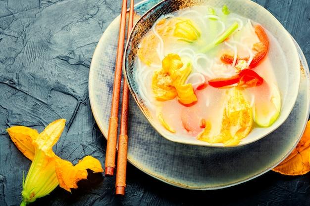 Zupa z makaronem ryżowym i kwiatami dyni.azjatycka zupa wegańska.