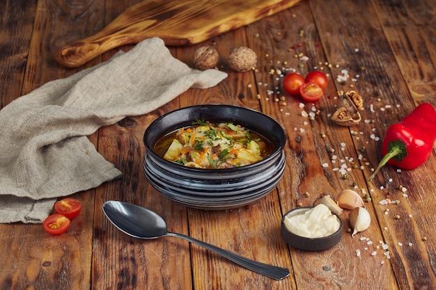 Zupa z makaronem w misce, łyżka na drewnianym stole