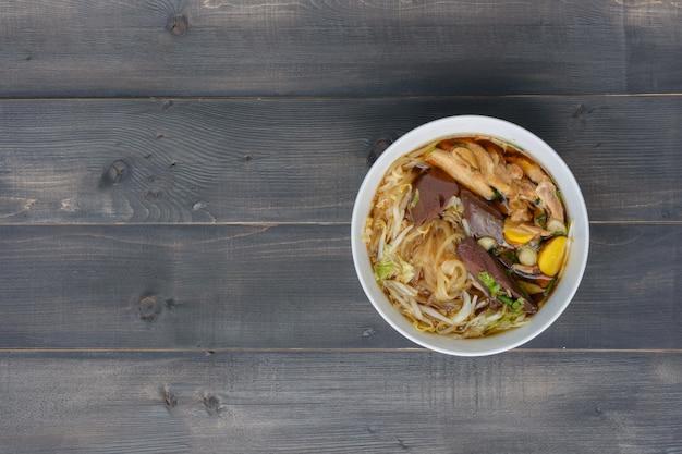 Zupa z makaronem w misce na drewnianym stole, widok z góry, tajskie lokalne potrawy
