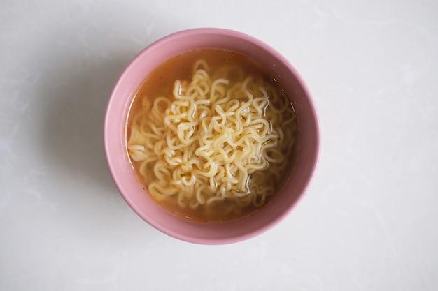 Zupa z makaronem w misce. widok z góry na białym tle
