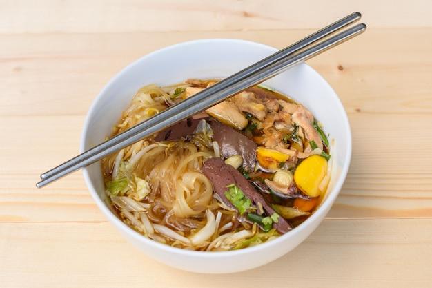 Zupa z makaronem z pałeczkami w misce na drewnianym stole, tajskie lokalne jedzenie