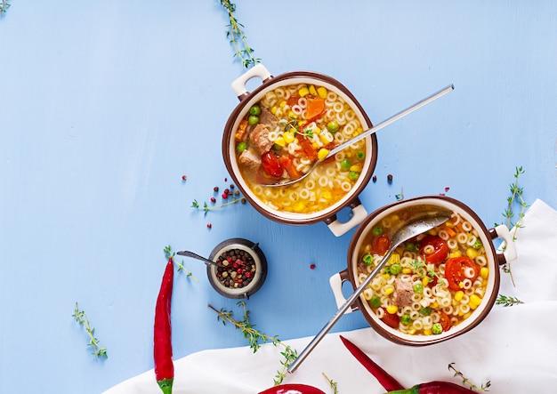 Zupa z małym makaronem, warzywami i kawałkami mięsa w misce na niebieskim stole. włoskie jedzenie.