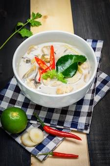 Zupa z mleka kokosowego z kurczakiem lub tajska zupa kokosowa z kurczakiem (tom kha gai) na drewnianym stole z obrusem, widok z blatu, tajskie lokalne jedzenie