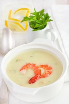 Zupa z owoców morza w misce i szklana woda z cytryną