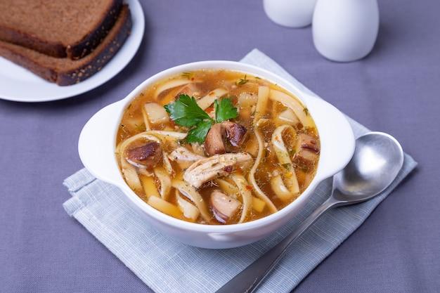 Zupa z pieczarkami, kurczakiem i makaronem na białym talerzu. tradycyjne danie rosyjskie. zbliżenie.