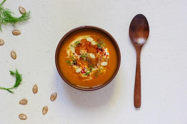 Zupa z pieczonej dyni i marchewki ze śmietaną, czarnym pieprzem i pestkami dyni, deską do krojenia i świeżymi plasterkami dyni, czarny chleb