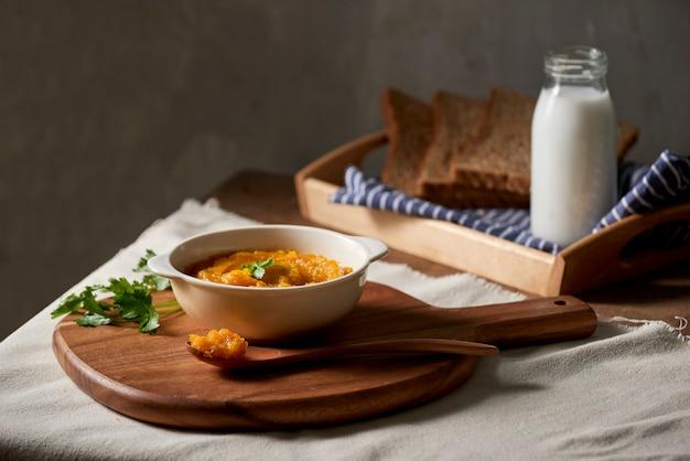 Zupa z pieczonej dyni i marchwi ze śmietaną i grzanką na drewnianym stole. skopiuj miejsce