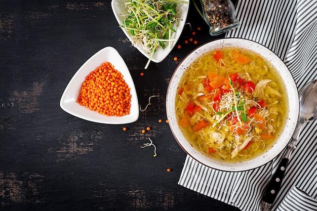 Zupa z soczewicy, marchewki, mięso z kurczaka, papryka, seler w misce. widok z góry