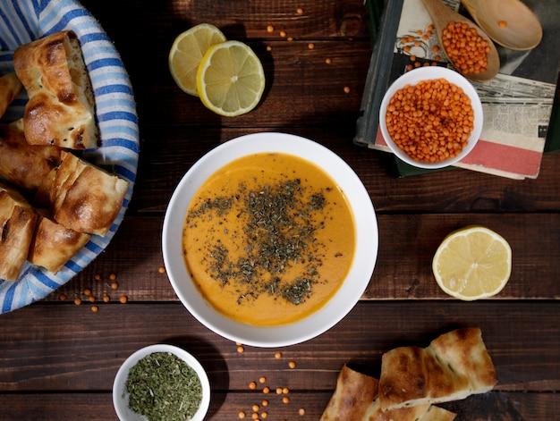 Zupa z soczewicy pomidorowej z ziołami w białej misce z chlebem, widok z góry