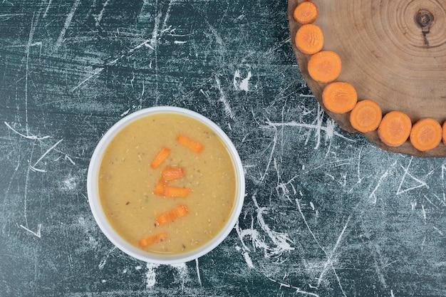 Zupa z soczewicy w białej misce i plastry marchwi. wysokiej jakości zdjęcie