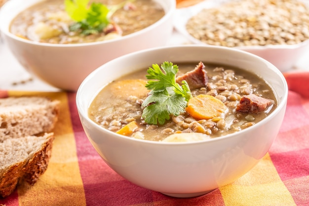 Zupa z soczewicy z kawałkami wędzonej karkówki, marchewką, ziemniakami i kolendrą. tradycyjne potrawy słowackie, czeskie lub wschodnioeuropejskie.