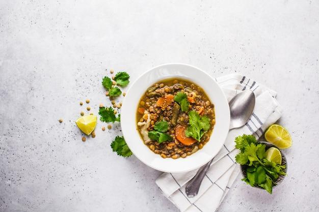 Zupa z soczewicy z warzywami w białym talerzu, białe tło, widok z góry. żywność na bazie roślin, czyste jedzenie.