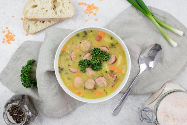 Zupa z soczewicy z wędzoną kiełbasą, ze świeżą bagietką lub pieczywem, w białej misce na jasnym betonie.