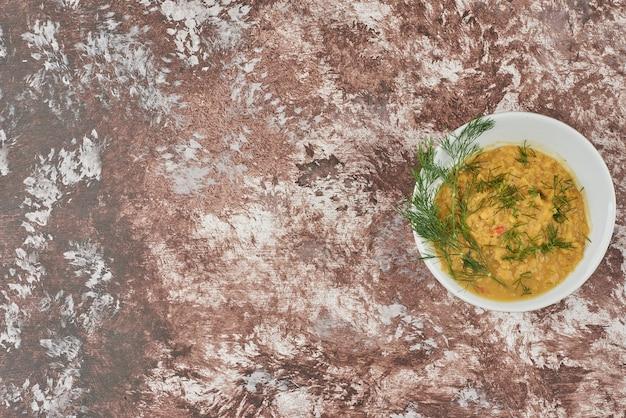 Zupa z ziołami w filiżance, widok z góry.