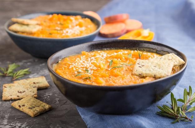 Zupa ze słodkich ziemniaków lub batata z sezamem i przekąskami w niebieskich ceramicznych misach na czarnej betonowej powierzchni. widok z boku, selektywne focus