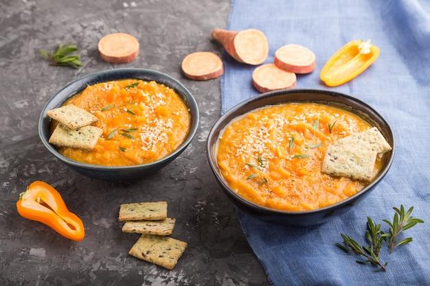 Zupa ze słodkich ziemniaków lub batata z sezamem i przekąskami w niebieskich ceramicznych misach na czarnej betonowej powierzchni. widok z boku, z bliska.