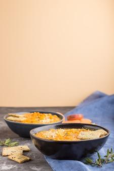 Zupa ze słodkich ziemniaków lub batata z sezamem i przekąskami w niebieskich ceramicznych misach