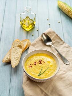 Zupa ze świeżego mleka kukurydzianego puree w białym talerzu na niebieskim tle ozdobiona peruką i młodą zieloną cebulą. orientacja pionowa. wysokiej jakości zdjęcie