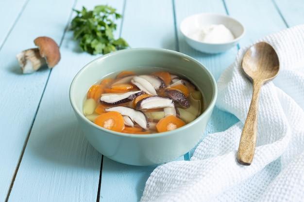 Zupa ze świeżych białych pieczarek i ziemniaków - tradycyjne danie kuchni rosyjskiej w glinianej misce na ciemnym tle drewnianych. widok z góry z miejsca kopii.