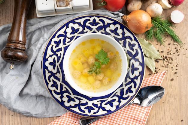 Zupa ziemniaczana z klopsikami drobiowymi, koperkiem i pietruszką na talerzu z tradycyjnym uzbeckim