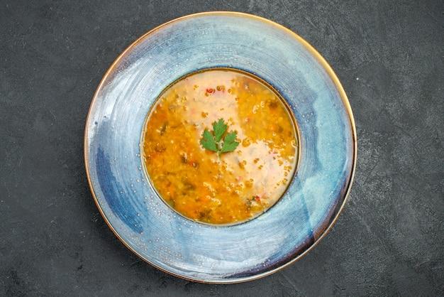 Zupa zupa z ziołami w niebieskim talerzu na stole