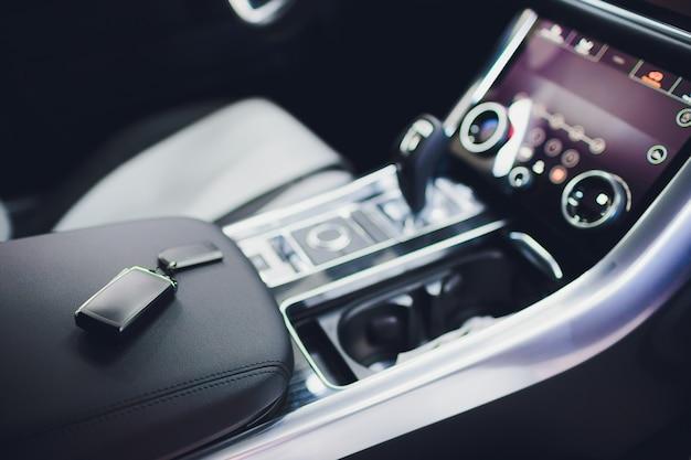 Zupełnie nowe kluczyki do samochodu na skórzanym zbliżeniu. koncepcja przemysłu samochodowego.